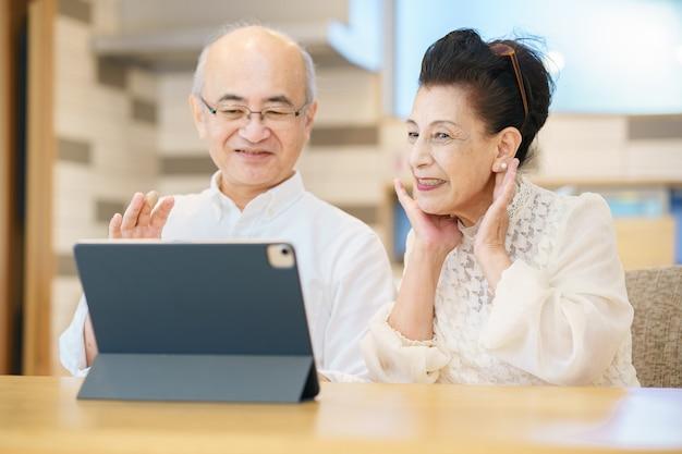 태블릿 pc로 온라인 커뮤니케이션을 즐기는 노부부