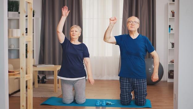一緒に体育を楽しんでいる年配のカップル。自宅での老人の健康的なライフスタイルの運動、トレーニングとトレーニング、自宅でのスポーツ活動