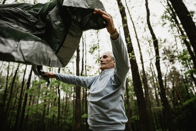 休暇を楽しんでいる年配のカップルがテントを張っています。自然に夏休みを過ごし、テントを張る大人たち。高齢者はキャンプしてテントを組み立てています