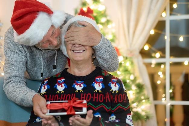 Старшие пары обмениваются рождественскими подарками у себя дома, улыбаясь