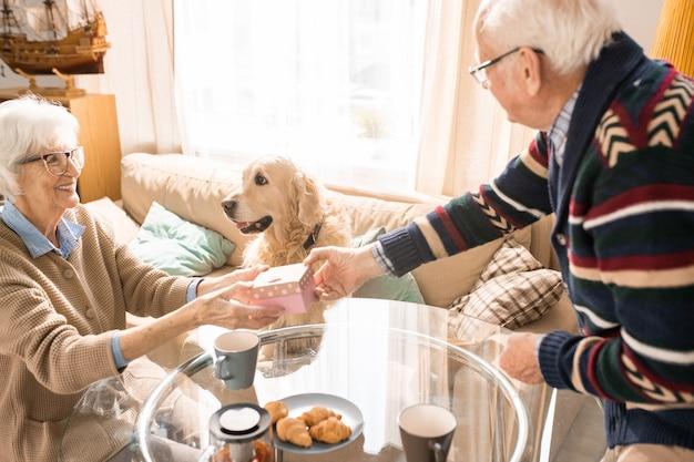 Пожилая пара обменивается подарками дома