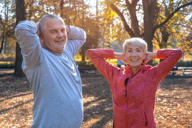 秋の公園で年配のカップルが一緒に運動