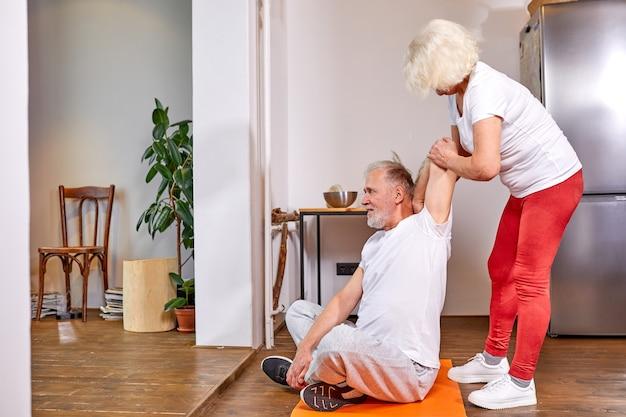 自宅で運動している年配のカップル、女性は床に座って、夫がストレッチするのを手伝います。幸福、健康的なライフスタイルの概念