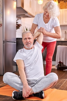 Senior couple exercising at home, woman help husband to stretch, sitting on the floor. wellbeing, healthy lifestyle concept