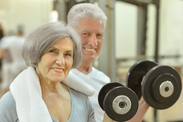 아령으로 체육관에서 운동하는 노인 부부