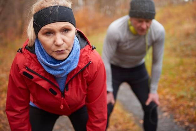 秋の森で運動する年配のカップル