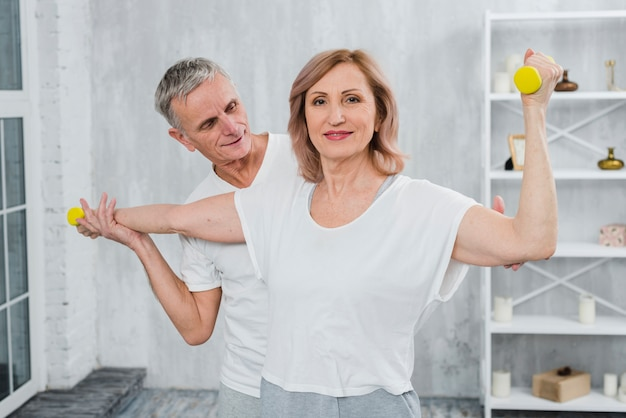 Senior couple exercising together at home with dumbbells