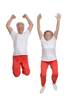 Senior couple exercising on a white background