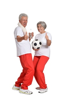 Senior couple exercising with ball and thumbs up on a white background