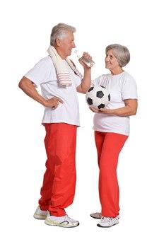 Senior couple exercising with ball on a white background