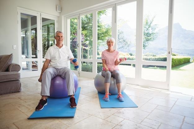 Senior couple exercising with dumbbells on exercise ball