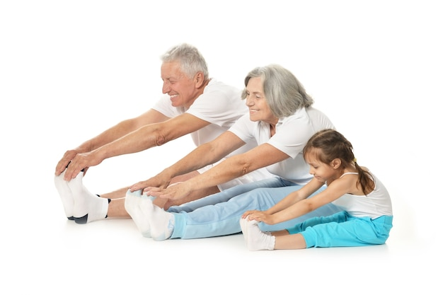Senior couple exercising with granddaughter isolated on white background