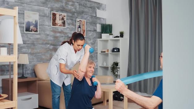 집에서 요가 매트에서 치료사와 함께 운동하는 수석 부부. 재택 지원, 물리 치료, 노인을 위한 건강한 생활 방식, 훈련 및 건강한 생활 방식