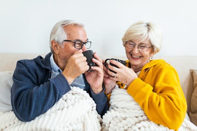 自宅のソファに毛布をかぶって座っている、居心地の良い温かい老夫婦。お茶を飲む老夫婦