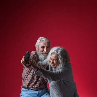 Senior couple fighting for the remote control against red background