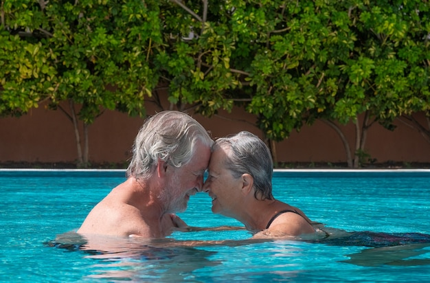 수영장 물에 머리를 맞대고 떠 있는 수석 부부, 여름 휴가를 즐기는 행복한 은퇴자
