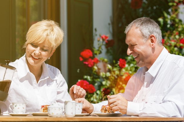 Senior couple in garden with coffee