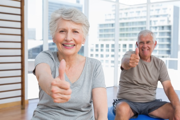 Senior couple gesturing thumbs up at medical gym