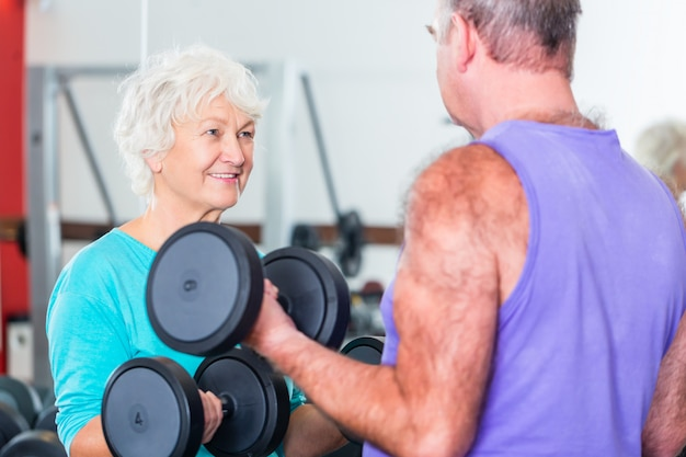 Senior couple in gym lifting dumbbell