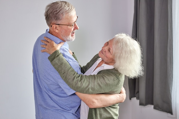 年配のカップルは家で踊るのを楽しんでいます、ロマンチックな成熟した白髪の男性と女性はエネルギッシュなアクティブを感じて家族の退職の週末を楽しんで、一緒に休日を過ごします