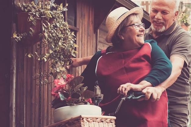 年配のカップルは、自宅の庭で自転車に乗って一緒に楽しんでいます。