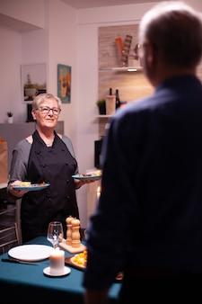キッチンで会話をしている年配のカップル。エプロンを着た年配の女性。老夫婦が話し、台所のテーブルに座って、食事を楽しんで、彼らの記念日を祝う