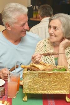 レストランで夕食をとる年配のカップル