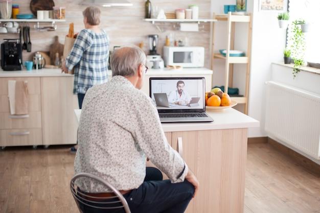 虐待について話している医師とのビデオ会議をしている年配のカップル。高齢者のためのオンライン健康相談薬の症状に関する病気のアドバイス、医師の遠隔医療ウェブカメラ。の医療
