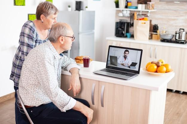 ノートパソコンのウェブカメラを使用して虐待を話している医師とのビデオ会議を持っている年配のカップル。高齢者のためのオンライン健康相談薬の症状に関する病気のアドバイス、医師の遠隔医療ウェブ