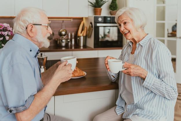집에서 아침 식사를 하는 노부부 - 아침에 노인들의 일상 프리미엄 사진