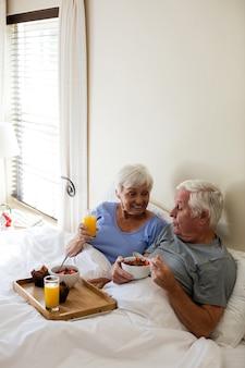 Senior couple having breakfast on bed in bedroom