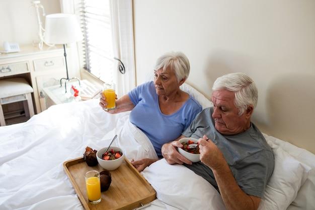 Senior couple having breakfast on bed in the bedroom