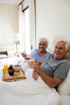 Senior couple having breakfast in the bedroom at home