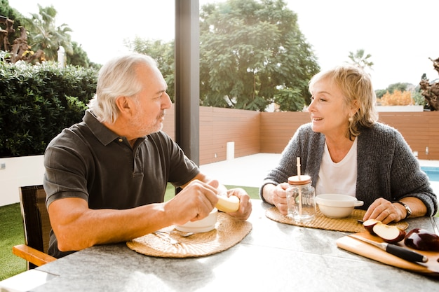 Senior couple having breakfast in garden