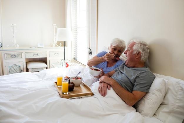 Старшая пара завтракает в спальне дома
