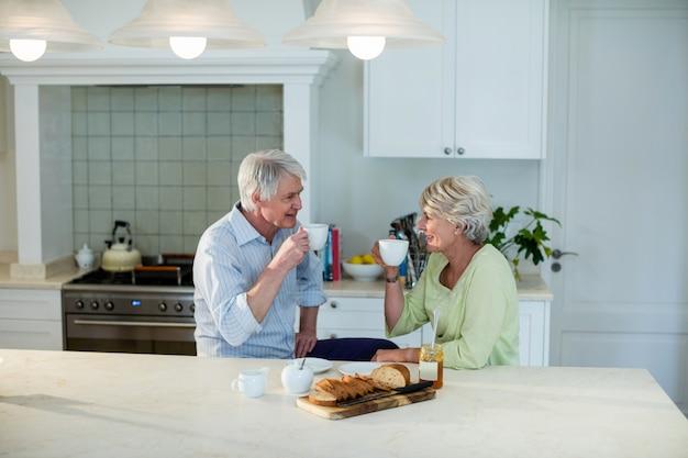 ダイニングテーブルでコーヒーを飲んでいる年配のカップル