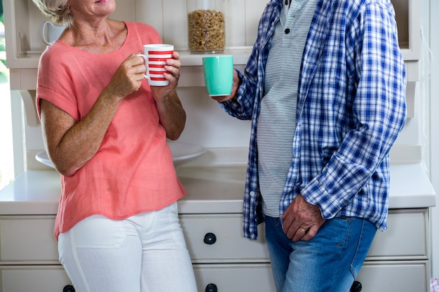 Senior couple having coffee in kitchen at home