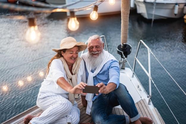夏休みにヨットで自分撮りを楽しんでいる年配のカップル-年配の男性の顔に主な焦点