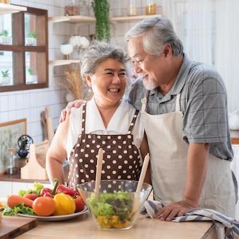 年配のカップルが健康食品とキッチンで楽しんで-引退した人が自宅で食事を調理する男と女のバイオ野菜とランチを準備-成熟した面白い年金受給者と幸せな高齢者の概念。