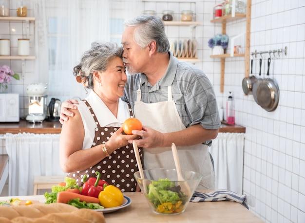 年配のカップルが健康食品とキッチンで楽しんで-引退した人が自宅で男と女のバイオ野菜でランチを準備して食事を調理-成熟した面白い年金受給者と幸せな高齢者の概念。