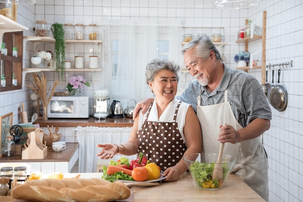 Senior couple having fun in kitchen with healthy food - retired people cooking meal at home with man and woman preparing lunch with bio vegetables - happy elderly concept with mature funny pensioner.
