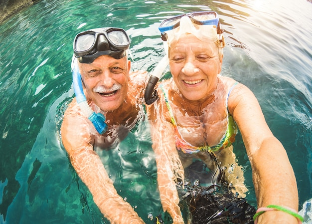 Senior couple having fun snorkeling at tropical beach