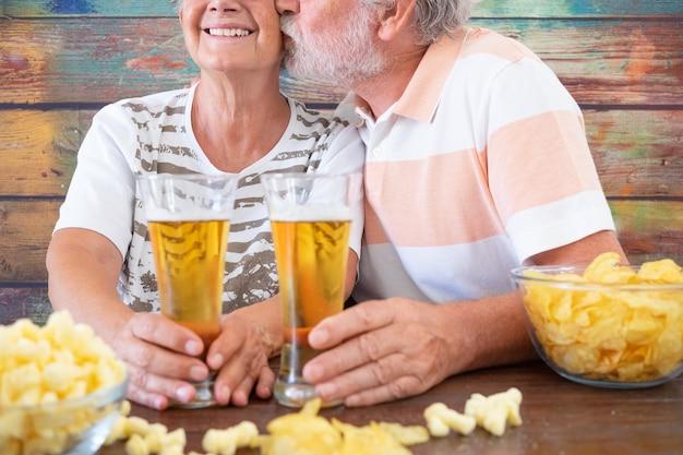 맥주와 팝콘을 가지고 노는 노부부. 남편이 아내에게 키스합니다. 나무 테이블에 앉아서 웃고 있습니다. 레져 활동