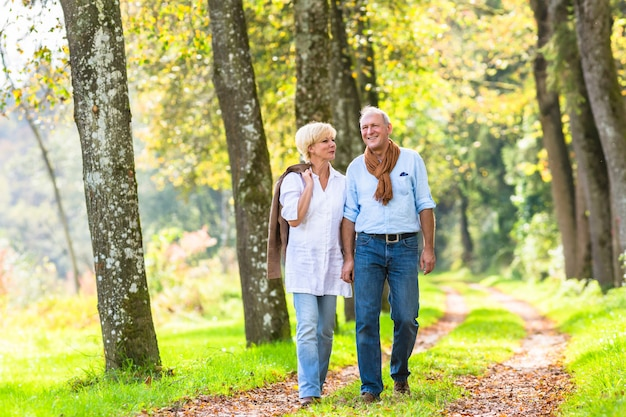 Senior couple having leisure walk in woods