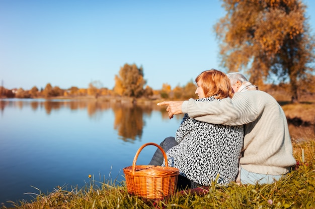 Senior couple having picnic by autumn lake happy man and woman hugging