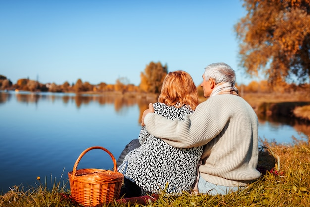 Senior couple having picnic by autumn lake.