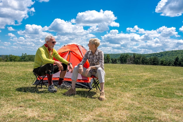 Senior couple having a rest in the field with a tent