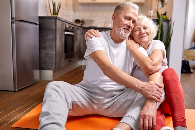 Senior couple having rest on the floor after yoga exercises, in sportive wear, and smile