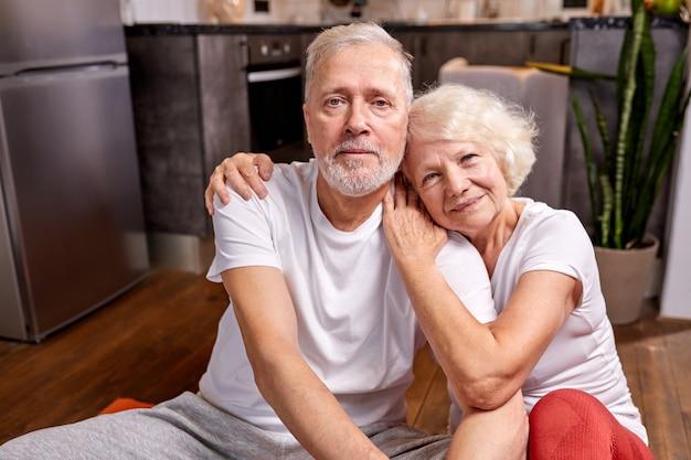 ヨガの練習の後、スポーティーな服装で床で休んでいる年配のカップル