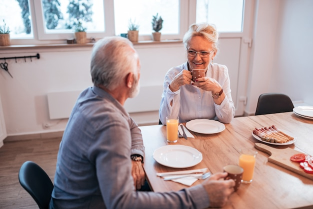 Senior couple having sitting at the table at home, eating breakfast.